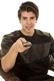 A man sitting pointing a remote control smiling Royalty Free Stock Photography