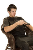 A man sitting pointing a remote control to the side Royalty Free Stock Photo