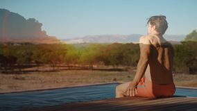 Man sitting on a pool deck. Digital composite of a man sitting on a pool deck with a view of trees and mountains stock video