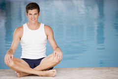 Man sitting poolside smiling Stock Images