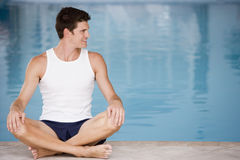 Man sitting poolside smiling. Away from camera Royalty Free Stock Image