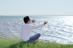 Man sitting at precipice and looking on the sea Stock Photos