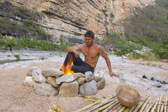 Man sitting at primitive campsite with fire stock photo