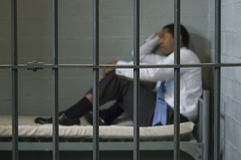 Man Sitting In Prison Cell Royalty Free Stock Photography