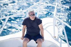 Man sitting on the prow of a boat Stock Photography