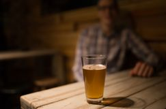 A man is sitting in a pub in front of a craft beer. Smiling, having fun Stock Images