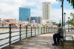 Man Sitting on a Public Bench with a View of Urban Singapore Royalty Free Stock Photo