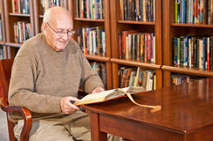 Man Sitting and Reading Book at Library Table Stock Image