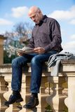 Man sitting reading a newspaper on a stone wall Stock Photo