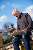 Man sitting reading a newspaper on a stone wall Stock Images