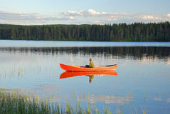 Man sitting in a red canoe on a lake in Finland at sunset. Man sitting in a red canoe on a lake in Finland and fishing at sunset Royalty Free Stock Images