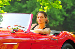 Man sitting in a red car. Long hair guy sitting in a classic red convertible car royalty free stock photography