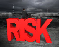 Man sitting on red risk word facing dark storm ocean Royalty Free Stock Photos