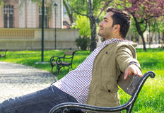 Man sitting and relaxing on bench in forest Stock Images