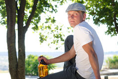 Man sitting relaxing with a bottle of alcohol Royalty Free Stock Photography