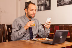 Man sitting in restaurant with laptop,and phone Royalty Free Stock Photo