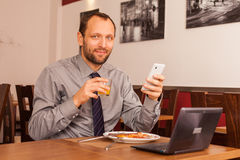 Man sitting in restaurant with laptop,and phone Stock Image