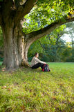 Man is sitting resting under tree Royalty Free Stock Photo