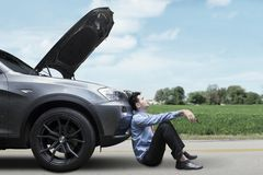 Man sitting on the road with broken car Royalty Free Stock Photography