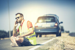 Man sitting on the road, talking by phone after a car breakdown. royalty free stock image