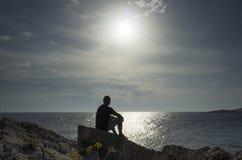 Man sitting on rock close the ocean in Croatia at sunset. Man sitting on rock close the ocean in Croatia. Looking at sea and sun. Nice, calm and peaceful photo Royalty Free Stock Photos