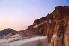 Man sitting on rock in desert. Man sitting on peak of mountains in desert Royalty Free Stock Images