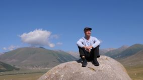 Man sitting on rock and enjoying beautiful mountain landscape at travel stock video