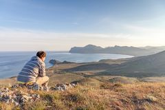 Man sitting on a rock on a hill above the city meditating and watching the sunset. Horizontal Stock Photography