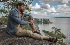 man is sitting on the rock and looking into the distance Royalty Free Stock Image
