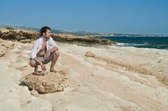 Man sitting on rock looking at sea Royalty Free Stock Photography
