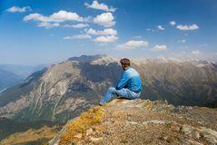Man sitting on the rock on mountain and blue sky background Royalty Free Stock Images