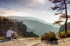 Man sitting on  rock in mountain and watching sunrise stock photo