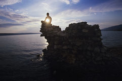 Man Sitting On Rock Overlooking Ocean. Young man sitting on rock overlooking ocean Royalty Free Stock Photos