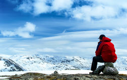 Man sitting on rock. S and looking at the snow-covered hills. Blue sky with clouds. Norway Stock Image