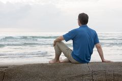 Man sitting on a rock at the sea Stock Photography