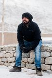 Man Sitting on Rock Wearing Black Jacket Royalty Free Stock Image