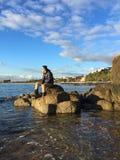 Man sitting on rocks on beach. Looking away stock image