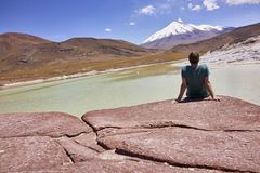 Man Sitting on the Piedras Rojas in Chile and Gazing at the Ande. A man sitting on rocks and gazing into the distance with a vista of snow capped Andes in the Royalty Free Stock Photography