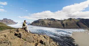 Man sitting on rocks overlooking Skaftafellsjokull part of Vatnajokull glacier in Skaftafell national park, Iceland.  stock photos