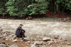 Man sitting on rocks of rough river Stock Image