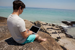 Man sitting on the rocks and using laptop at the sea coast Stock Photography