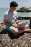 Man sitting on the rocks and using laptop at the sea coast Stock Image