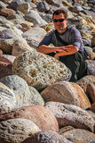 Man sitting on a rocks. Young man sitting on large boulders on the coastline in northern New Zealand royalty free stock photography