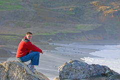 Man Sitting on Rocky Beach. Handsome man wearing red coat sitting on rocky beach contemplating thoughts royalty free stock photos