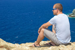 Man sitting on rocky cliff on sea coast Stock Photos