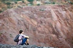 Man sitting on rocky cliff Stock Image