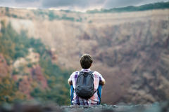 Man sitting on rocky cliff. Young tourist man with backpack sitting on rocky cliff and enjoying beautiful view Royalty Free Stock Photography