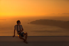 Man sitting on the roof at sunset Stock Image