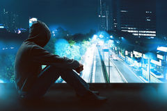 Man sitting on the rooftop. At night Stock Image