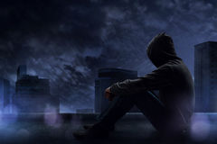 Man sitting on the rooftop. In a rainy night Stock Photos